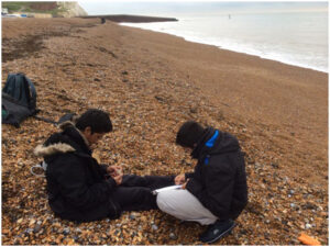 Students measure the dimensions of pebbles along a transect